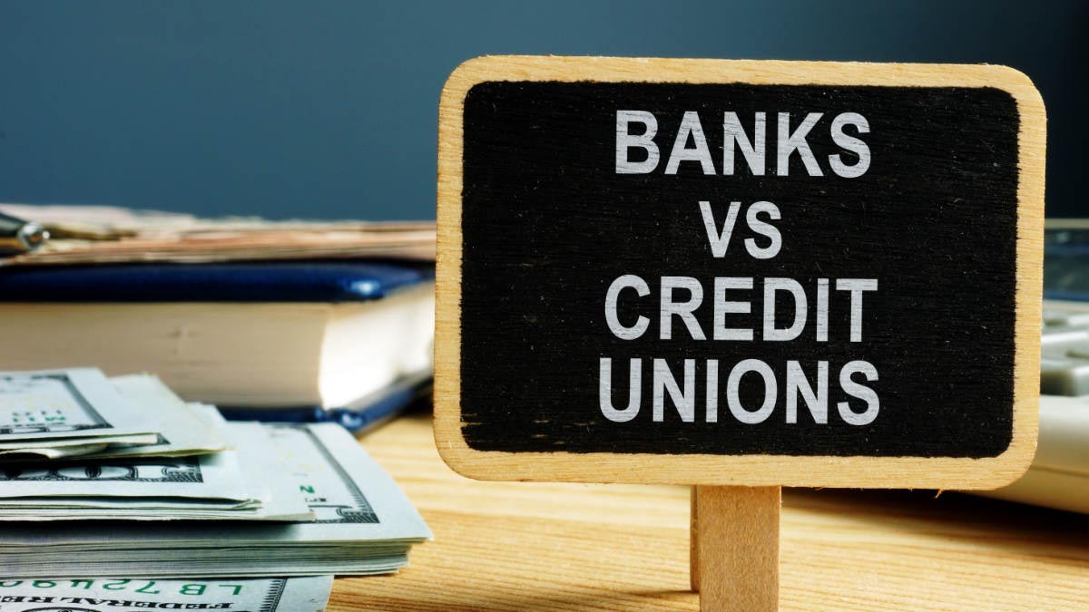 Banks Vs. Credit Unions Sign with a stack of money
