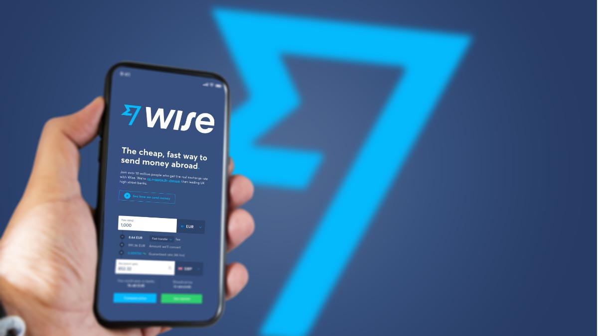 Wise App on phone in hand with logo in the background