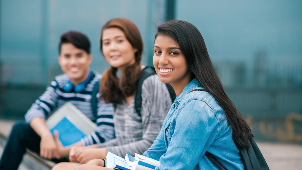 Female Indian student smiling with friends in background