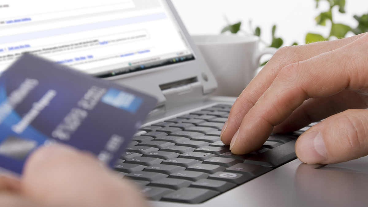 man using credit card on laptop